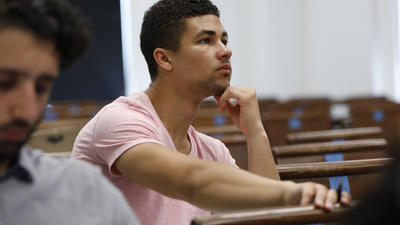 Male students listening in class.