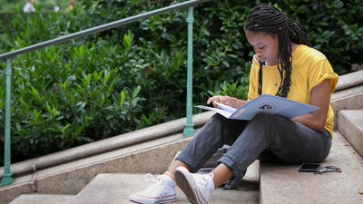 Female student reads, sitting on steps in a campus green space.