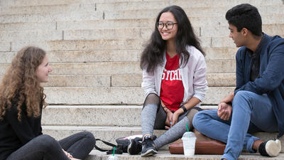 Three high school students sit on the Low Library steps.