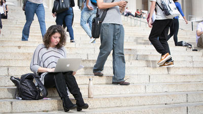 Adults & Professionals - a woman using a laptop, seated on the Low Library steps.