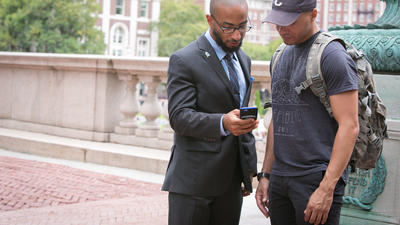 Two students look at a phone in an outdoor campus setting.