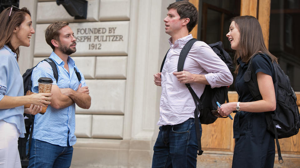 Four students standing and conversing in front of Pulitzer Hall.