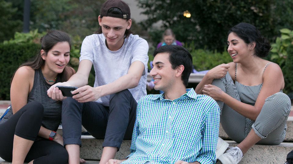 Four students sitting together looking at one student's phone, while outside on campus.